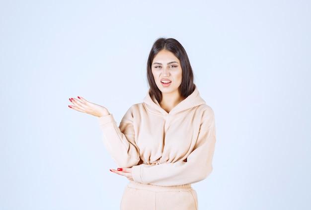 Junge frau in einem rosa kapuzenpulli, der etwas in ihrer offenen hand präsentiert