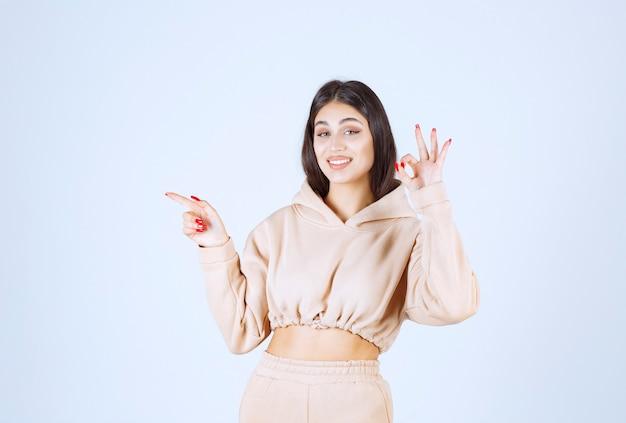 Junge frau in einem rosa kapuzenpulli, der gutes handzeichen zeigt
