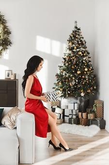 Junge frau in einem roten abendkleid hält weihnachtsgeschenkbox über neujahr