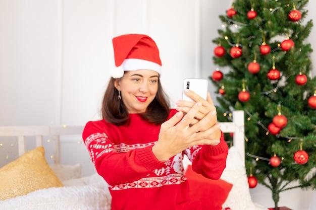 Junge frau in einem roten pullover, der ein selfie nahe dem weihnachtsbaum nimmt