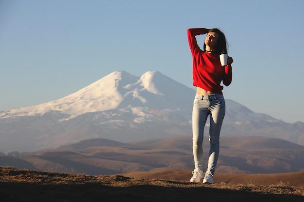 Junge frau in einem roten pullover, der gegen die verschwommenen berge steht und die ersten sonnenstrahlen mit einer tasse tee in ihrer hand genießt