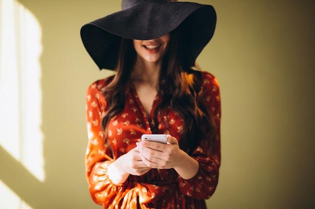 Junge frau in einem schönen kleid unter verwendung des telefons und online kaufen