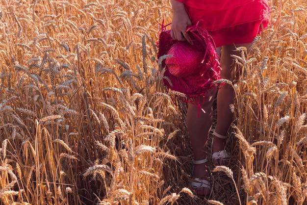 Junge frau in einem schönen roten kleid, das das sonnige wetter in einem weizenfeld genießt