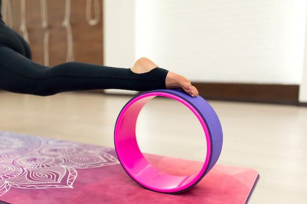 Junge frau in einem sportkleidungsyoga trainiert mit einem yoga drehen herein die turnhalle. stretching und wellness lifestyle