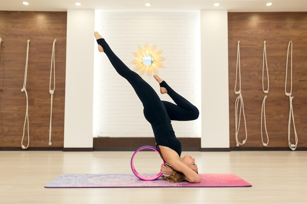 Junge frau in einem sportkleidungsyoga trainiert mit einem yoga drehen herein die turnhalle