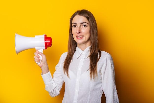 Junge frau in einem weißen hemd hält ein megaphon in ihren händen auf einem gelben hintergrund