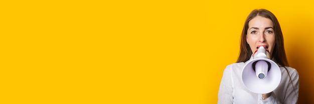 Junge frau in einem weißen hemd schreit in ein megaphon auf gelbem hintergrund