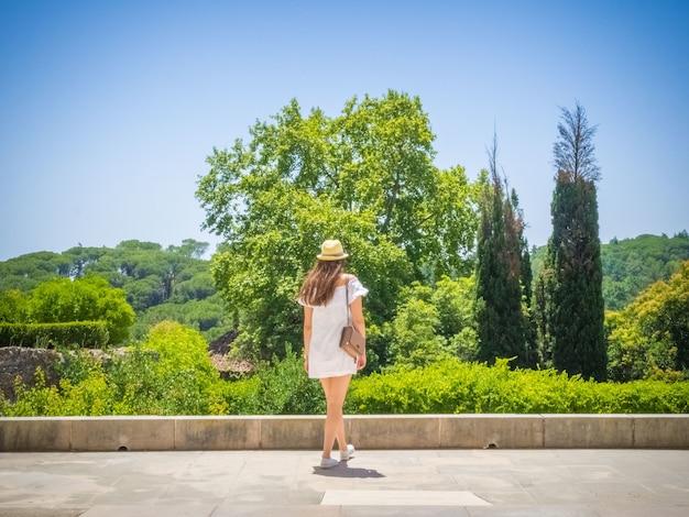 Junge frau in einem weißen kleid, das in einem park geht, der die schöne ansicht eines grünen waldes genießt