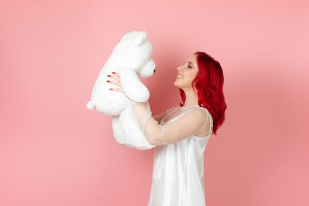 Junge frau in einem weißen kleid und mit den roten haaren, die einen großen weißen teddybär betrachten
