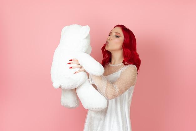 Junge frau in einem weißen kleid und mit roten haaren bläst einen kuss zu einem großen weißen teddybär