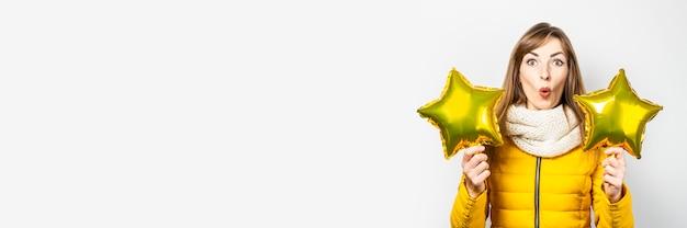 Junge frau in einer gelben daunenjacke und hut lokalisiert