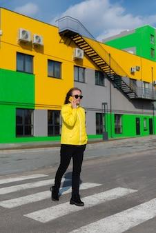 Junge frau in einer gelben jacke mit smartphone in der stadt gegen gebäude in hellen farben