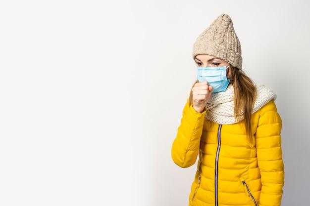 Junge frau in einer gelben jacke und einem hut mit einer medizinischen maske lokalisiert
