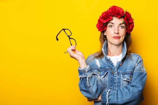 Junge frau in einer jeansjacke und einem kranz aus roten blumen auf ihrem kopf hält brille an einer gelben wand.