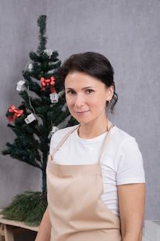 Junge frau in einer küchenschürze gegen weihnachtsbaumhintergrund. vertikaler rahmen.