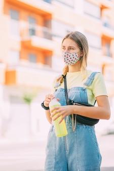 Junge frau in einer maske, die wasser trinkt und durch die stadt geht