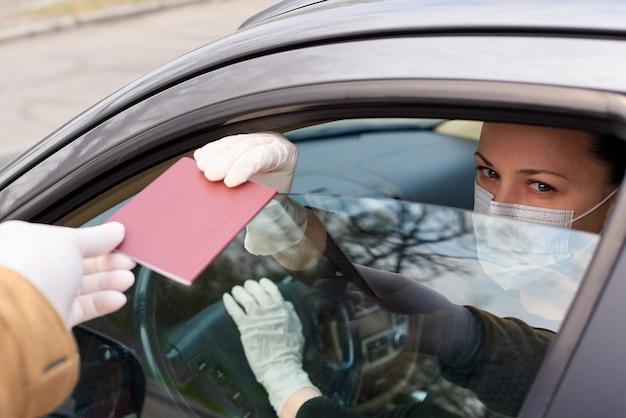 Junge frau in einer maske mit einem pass in einem auto. überprüfen eines passes und einer erlaubnis zur bewegung in der stadt während einer epidemie. kontrollieren von fahrerdokumenten während der quarantäne in der stadt.