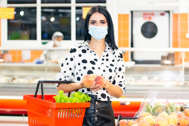 Junge frau in einer medizinischen einwegmaske kauft im supermarkt ein