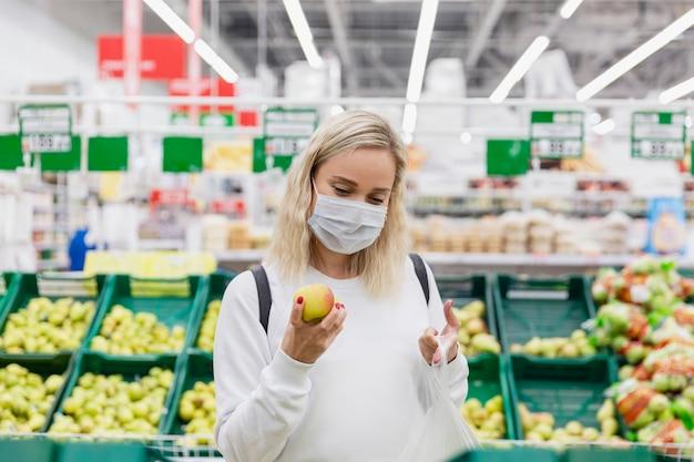 Junge frau in einer medizinischen maske wählt äpfel in einem supermarkt. gesundes essen. coronavirus pandemie.