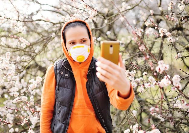Junge frau in einer orange jacke, die eine atemschutzmaske oder eine gesichtsmaske trägt, spricht über videolink auf einem smartphone
