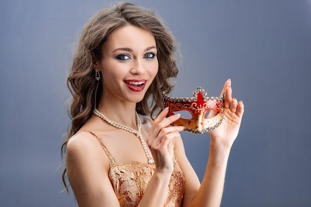 Junge frau in einer perlenhalskette überraschte, die kamera betrachtend und eine karnevalsmaske zeigend