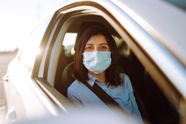Junge frau in einer schutzmaske, die im auto sitzt