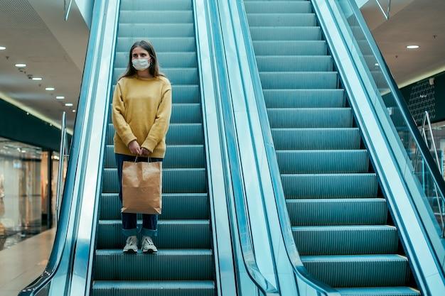 Junge frau in einer schutzmaske, die sich in einem einkaufszentrum bewegt. foto mit einem kopierraum