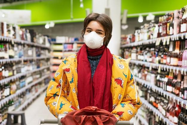 Junge frau in einer schutzmaske wählt alkohol in einem supermarkt, aktien werden unter quarantäne gestellt