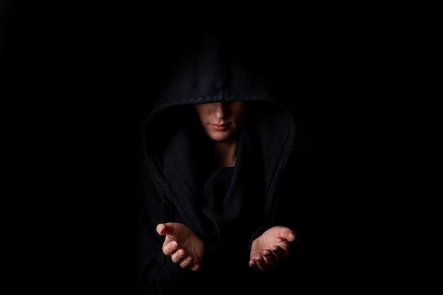 Junge frau in einer schwarzen kapuze mit offenen handflächen auf einem dunkelschwarzen hintergrund.