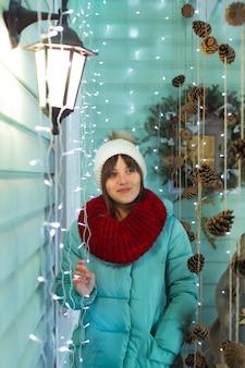 Junge frau in einer warmen mütze, einem schal und einer daunenjacke auf dem hintergrund der weihnachtsdekorationen
