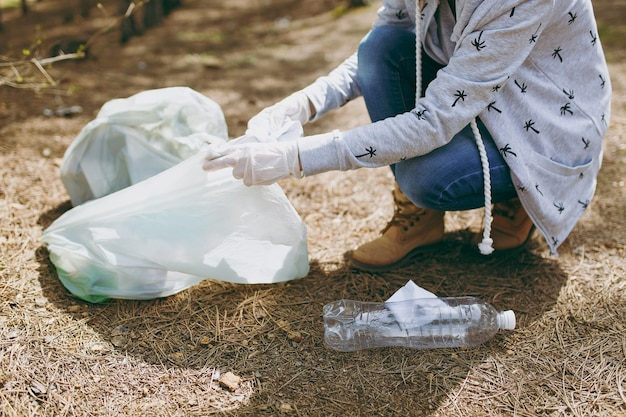 Junge frau in freizeitkleidung, handschuhe, die müll in müllsäcke im park säubern. problem der umweltverschmutzung