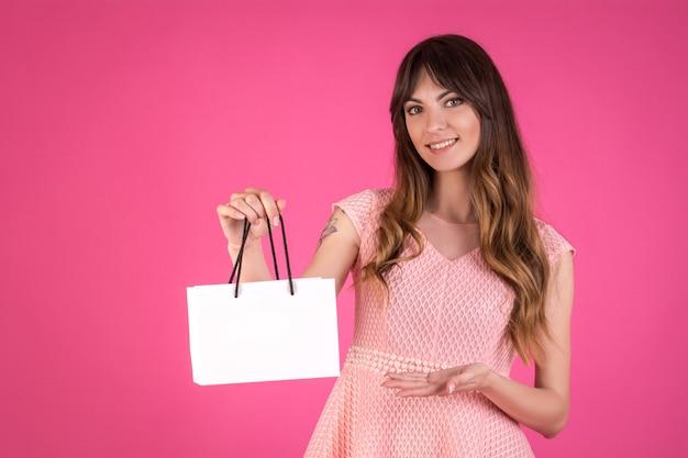 Junge frau in gekleidet in ein rosa kleid mit einer weißen geschenktüte