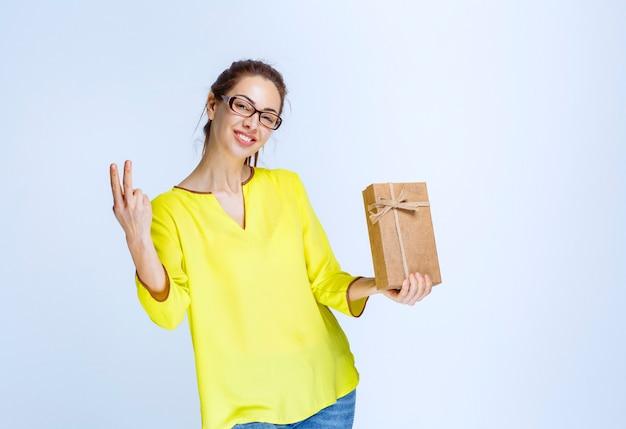 Junge frau in gelbem hemd, die eine geschenkbox aus karton hält und freudenhandzeichen zeigt