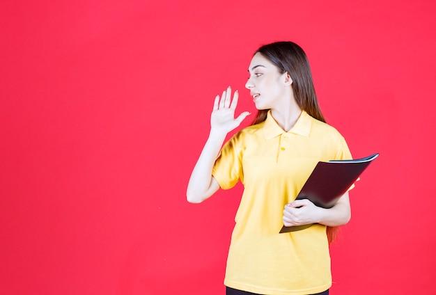 Junge frau in gelbem hemd, die einen schwarzen ordner hält, auf ihre kollegin zeigt und sie anruft