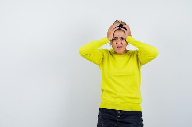 Junge frau in gelbem pullover und schwarzer hose, die hände an den kopf hält und gehetzt aussieht