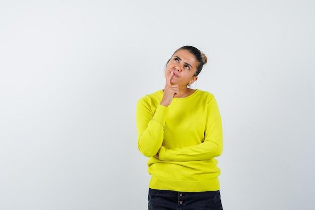 Junge frau in gelbem pullover und schwarzer hose, die in denkender pose steht und nachdenklich aussieht
