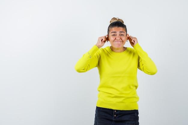 Junge frau in gelbem pullover und schwarzer hose, die mit den fingern die ohren streckt, die wangen aufbläht und amüsiert aussieht