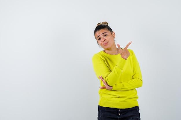 Junge frau in gelbem pullover und schwarzer hose, die nach rechts zeigt, während sie die hand am ellbogen hält und nachdenklich aussieht