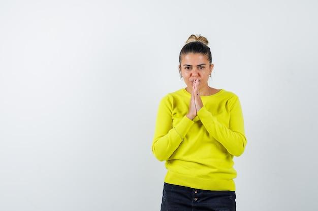 Junge frau in gelbem pullover und schwarzer hose, die namaste-geste zeigt und ernst aussieht