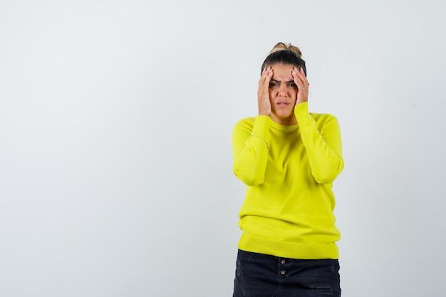 Junge frau in gelbem pullover und schwarzer hose, die sich die hände vors gesicht hält, eine grimasse verzieht und genervt aussieht
