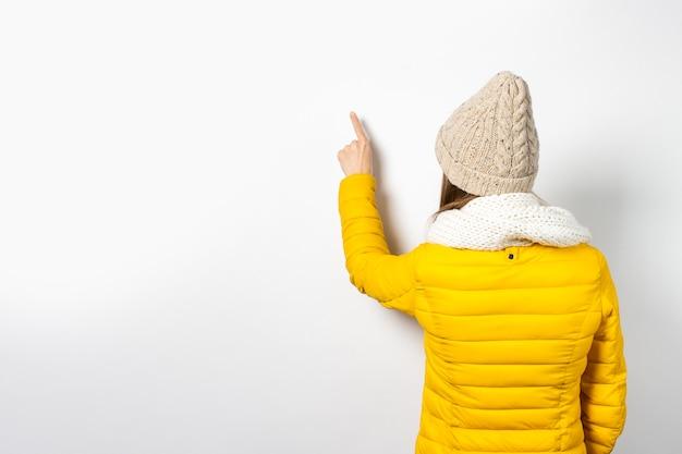 Junge frau in gelber daunenjacke und hut zeigt mit dem finger auf etwas an der wand.
