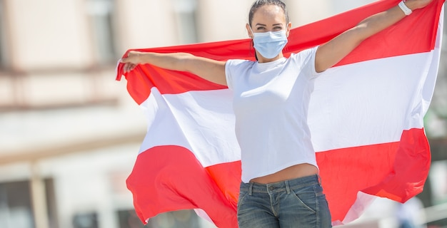 Junge frau in gesichtsmaske hält österreichische flagge auf der straße.