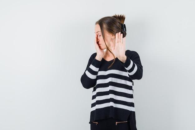 Junge frau in gestreiften strickwaren und in schwarzen hosen, die stoppschild zeigen und einen teil des gesichts mit der hand bedecken und bedrückend aussehen