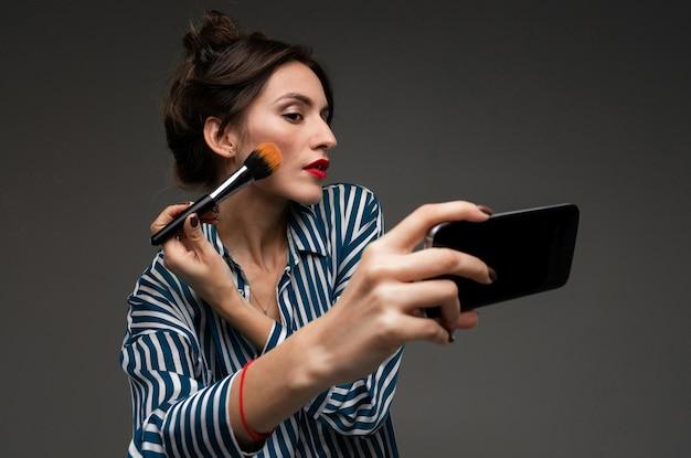 Junge frau in gestreifter bluse unter verwendung des schwarzen mobiltelefons anstelle des spiegels und des setzens auf rouge mit der make-upbürste lokalisiert