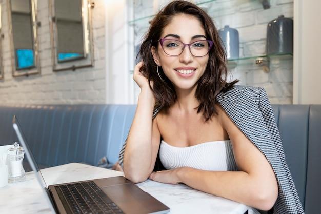 Junge frau in gläsern mit laptop in einem café. lächelnde brünette, die aus der ferne arbeitet.