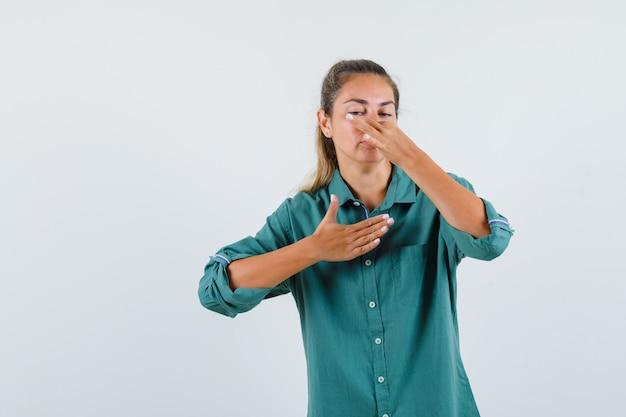Junge frau in grüner bluse kneift nase wegen schlechten geruchs und sieht genervt aus