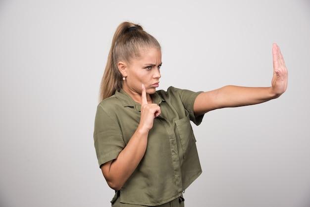 Junge frau in grüner jacke, die ihre hand zur ablehnung anbietet.