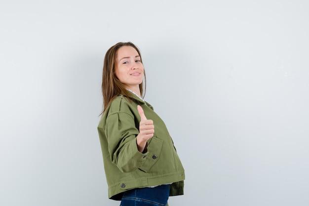 Junge frau in grüner jacke, die sich daumen zeigt und selbstbewusst aussieht.