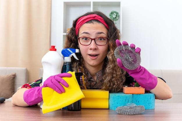 Junge frau in gummihandschuhen, die kamera erstaunt und glücklich am tisch mit reinigungsmitteln und werkzeugen im hellen wohnzimmer sitzend betrachten