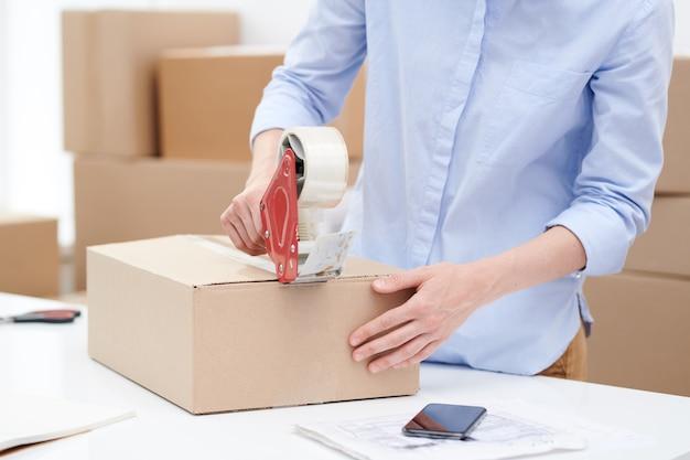 Junge frau in hellblauer freizeithemd-verpackungsbox mit bestellung des kunden und kleben mit klebeband